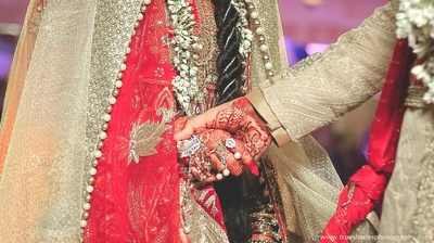 Red weding lehenga embellished with floral zari buttis, beads, sequins, and white and gold pearled kinaari