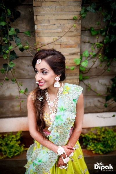 The bride reflecting her beautiful floral jewellery at her Mehndi function