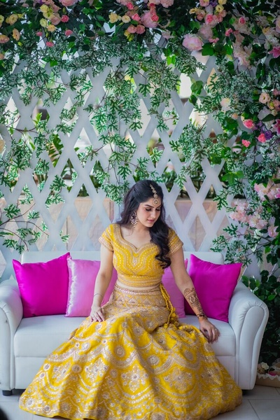 The bride in a pretty yellow lehenga for her mehendi