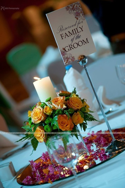 Table center piece. Signage ideas. Cangle decorated with Rose flowers