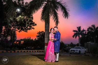 The beautiful bride and groom posing against a multi-hued sky.