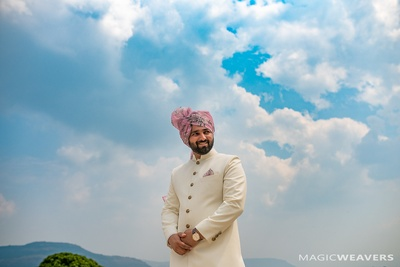 The groom ready in ivory sherwani and floral safa