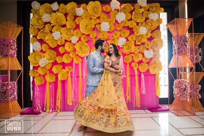 the bride and groom dancing at their mehendi ceremony against a colourful backdrop of pink and yellow