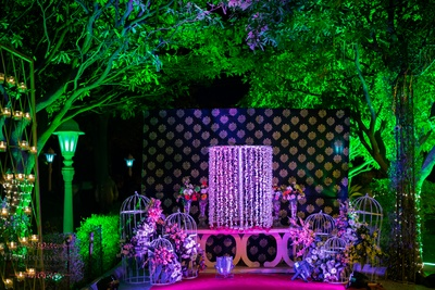 Photo booth station setup with cages adorned with clustered fresh flower arrangement