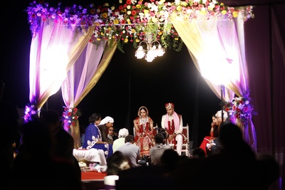 Vedi mandap decorated with purple and gold drapes and a clustered floral arrangement