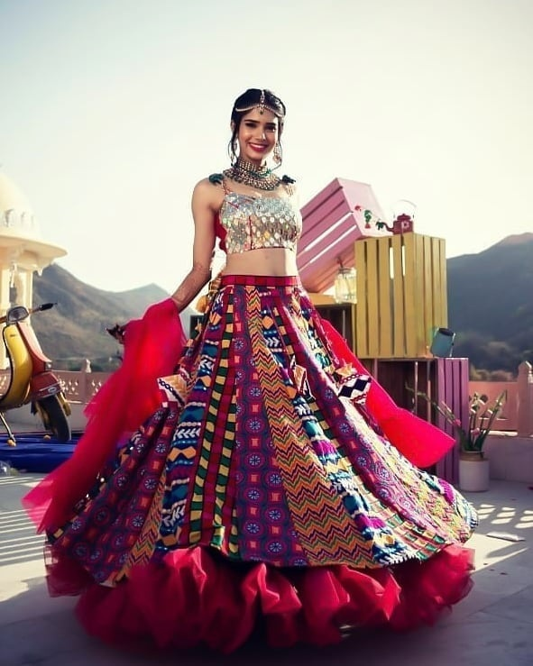ffc7b15a02a8 This is a pretty bride in one of the most eye-catching colourful lehenga  skirt paired with a crop top with heavy mirror work on it!