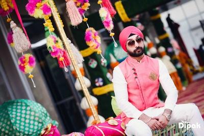 Groom wearing a fuschia nehru jacket for the mehndi ceremony at JW Marriott, Chandigarh