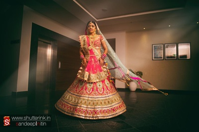Pink wedding lehenga embellished with aqua embroidered motifs and intricate detailing styled with double dupatta