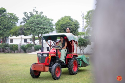 The bride and groom having some fun on a tractor