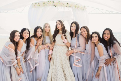 Bride and bridesmaids pose together at the Cancun Beach in matching wedding lehengas
