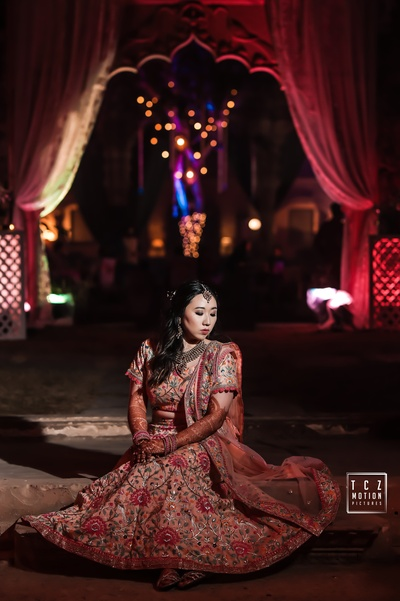 the bride looking stunning in a peach embroidered lehenga at her sangeet ceremony