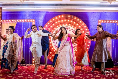 a candid capture of the bride and groom dancing with their family at their sangeet