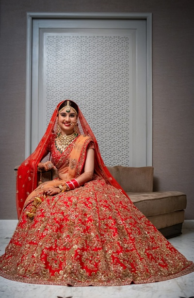The bride flaunts a traditional red lehenga with heavy embellishments and a sheer orange dupatta.