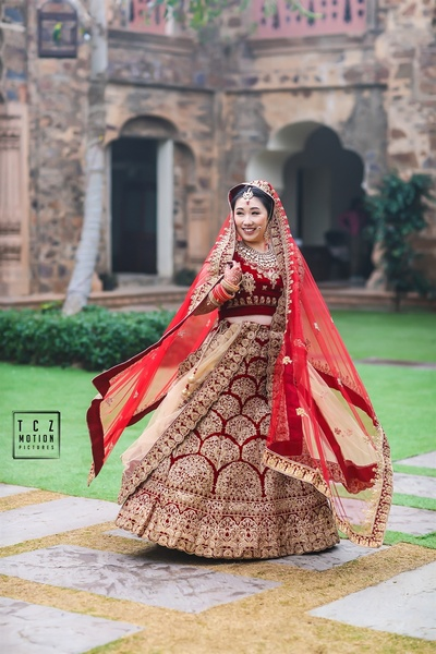 a beautiful picture of the bride twirling in her red lehenga