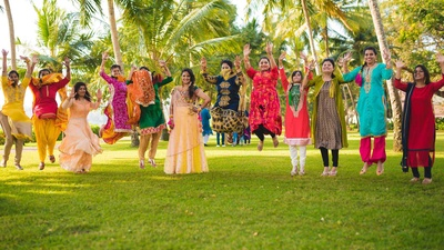 Bride and her bridesmaids dressed up in colorful outfits for the mehndi day.