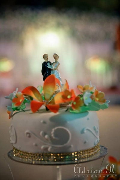 White ornated wedding cake adorned with floral topper