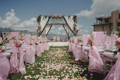 The mandap decorated with flowers while the chairs have a pink sheen cloth tied to them