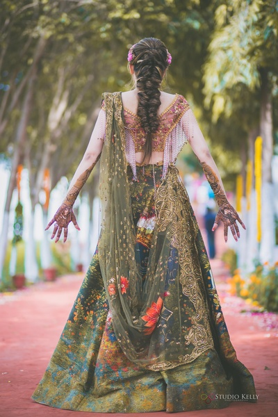 This bride looks absolutely stunning in her green lehenga and a mermaid braid.