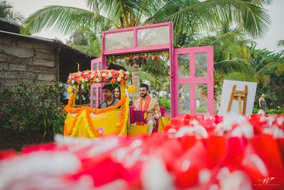 the bride and groom entering the mehendi ceremony in a rickshaw
