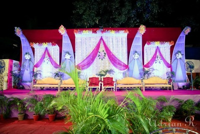 Wedding stage decorated with drapes, strings, and floral wall bouquets