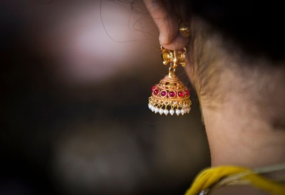 Gold jhumka studed with gemstones and pearls