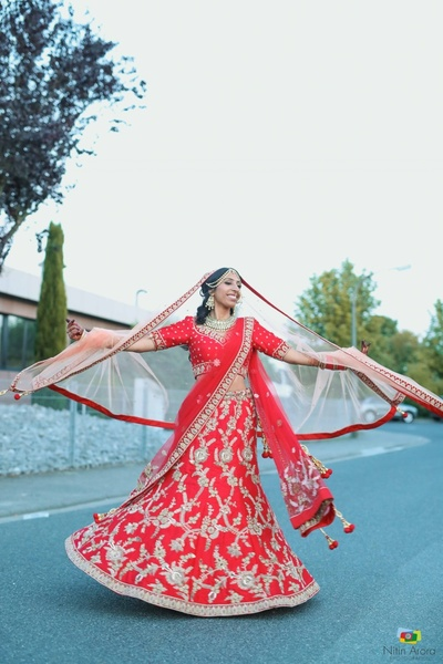 Bride in her red lehenga with silver zari work twirling