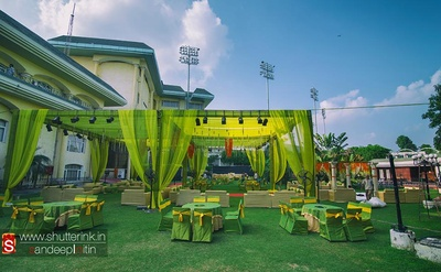 Wedding venue decked in parrot and forest green cabanas, table and chair covers, and lime arbour and tie backs