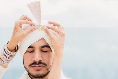 Groom getting ready for the wedding ceremony in his white attire and safa