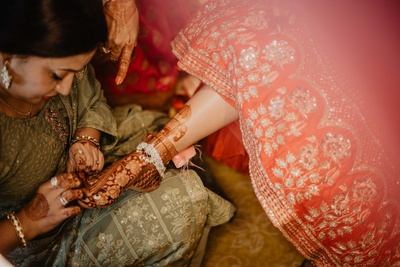 A candid shot of bride getting help in wearing her toe rings, an important element in the solah shringar.