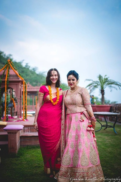 Bride and bridesmaid wearing color coordinated outfits for the wedding ceremony.