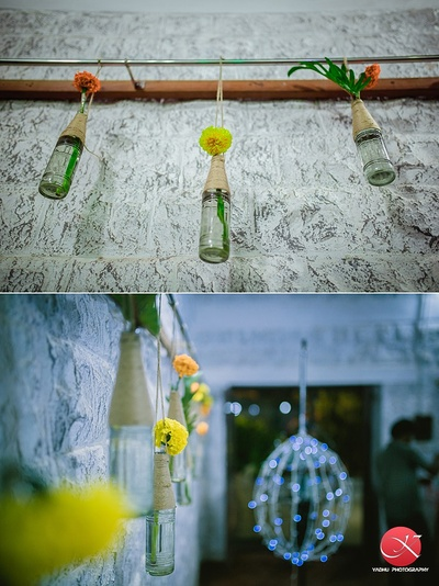 Passage of the wedding venue decorated with DIY glass bottles used as suspended on an iron rod