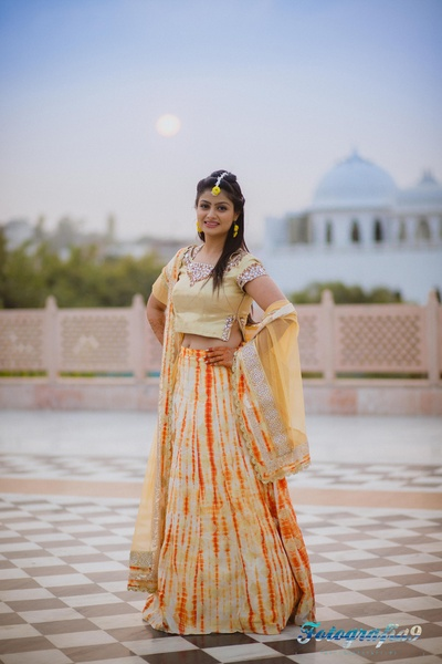 Orange and ivory tie dye lehenga with scalloped edging border, styled with matching floral jewellery