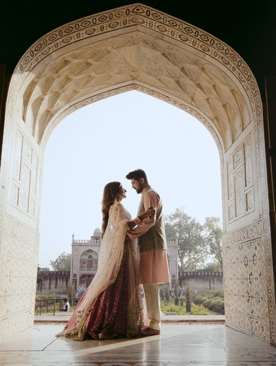 The photographer captures the couple as they strike a stunning pose under the archway!