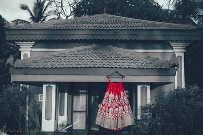 Red velvet Sabysachi lehenga embellished with embroidery and sequined motifs for the beach side wedding held at Goa Marriott