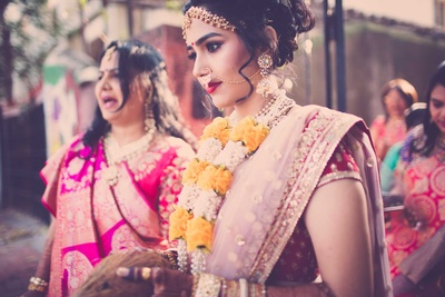 Traditional bride makes her way to the wedding mandap