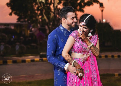The bride and groom share a light moment at their mehendi cereomony photo shoot!