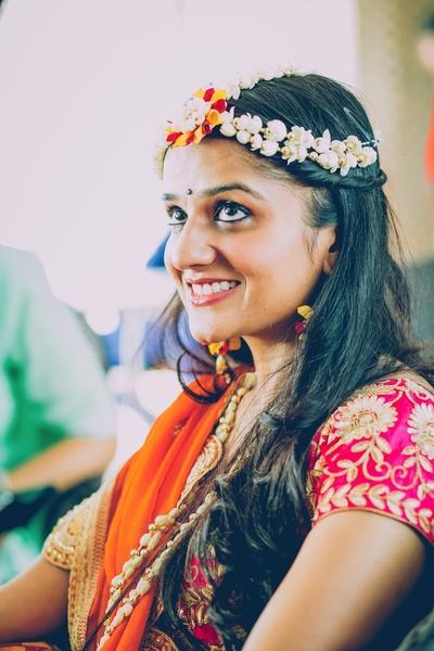 Bride Vasundhra looking extremely pretty in this colorful outfit styled with minimal floral jewellery for her Mehendi ceremony.
