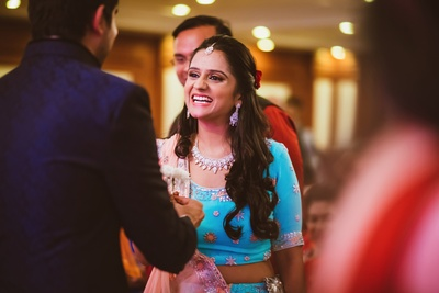 Bride Vasundhra looking pretty in this aqua blue lehenga with pastel pink dupatta styled with diamond earrings and necklace.