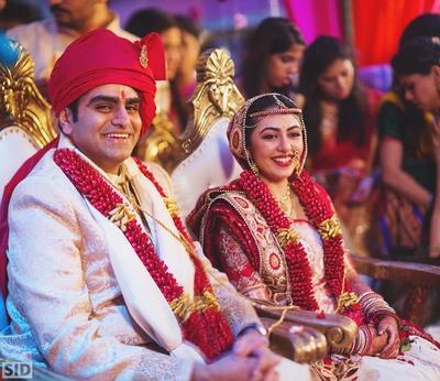 Meha and Vinay looking extremely happy and cheerful wearing those beautiful flower garlands!