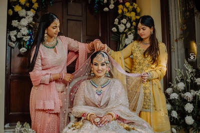 The bridesmaids dressing up the bride prior to her wedding ceremony!