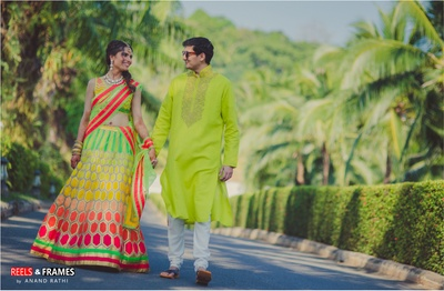 Motif patterned bridal wear of neon colors complementing the smart ensemble of the groom is shot at the sunny day