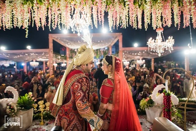 Bride and Groom stand after their varmala exchange under the mandap decor at Hotel Renaissance, Lucknow