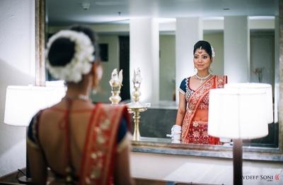 Red and blue designer wedding lehenga styled with minimal polki studded jewellery and light bridal makeup