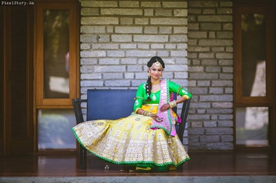 Bride Jeenal dressed up in beauiful yellow and green gotta pati lehenga with pink dupatta and gold jewellery.