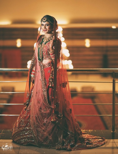 The bride in a gorgeous red lehenga captured right before the wedding