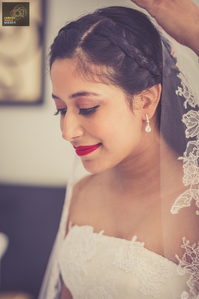 White off-shoulder wedding gown embellished with floral applique styled with brown eye shadow, red lipstick and diamond studded dainty earrings