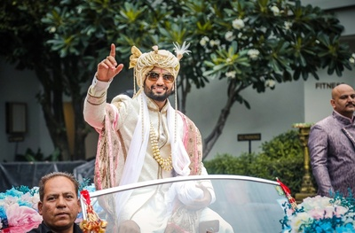 The groom leading his baraat in a vintage car