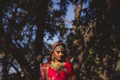 Red and pink Sabyasachi wedding lehenga styled by pankh jewellery set and studded with kundan and meena kari