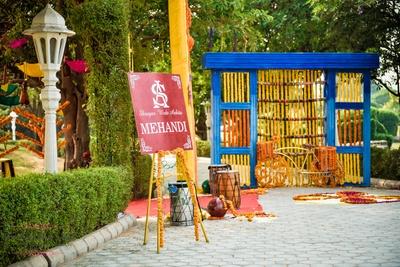 Mehendi ceremony decor with genda flowers, umbrella and dhol