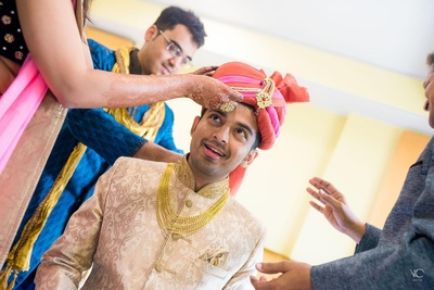 Groom wearing a beige sherwani with a traditional turban with kalgi and a gold multi strand chain.